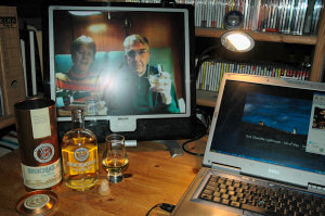 Picture of a whisky being poured seen on a monitor, a bottle and a glass standing in front of it