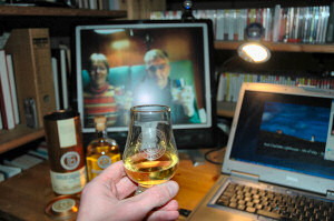 Picture of a dram of whisky being held up in front of a monitor, two people doing the same on the monitor