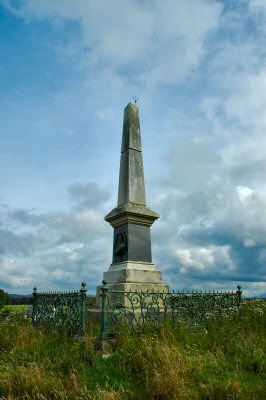 Picture of a monument / obelisk for John Francis Campbell on Islay, surrounded by a fence