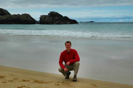 Picture of a person kneeling on the sand in a bay, the sea in the background (Lossit Bay, Islay