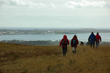 Picture of walkers descending a hill, a sea loch and a village in the distance