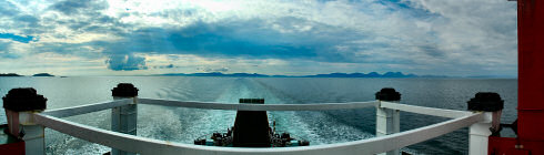 Picture of a panoramic view looking back from a ferry over three islands