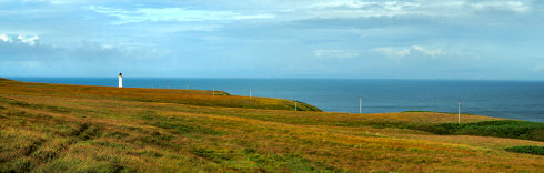 Picture of a wide landscape with telegraph poles leading to a lighthouse in the distance