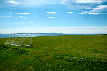 Picture of a football pitch next to a sea loch und a bright blue sky