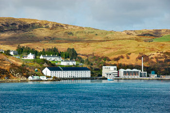 Picture of the whitewashed buildings of a distillery near the shore (Caol Ila on Islay)