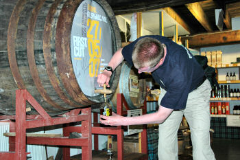 Picture of a man filling a whisky bottle from the cask, using a valinch