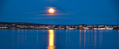 Picture of the moon rising over a coastal village