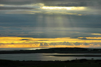 Picture of a sunset on a partly cloudy sky, the sea in the background, a loch (lake) in the foreground