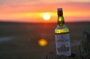 Picture of a whisky bottle in the last sunlight during a sunset
