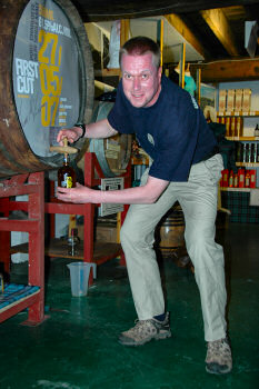 Picture of a man filling a whisky bottle from a cask using a valinch