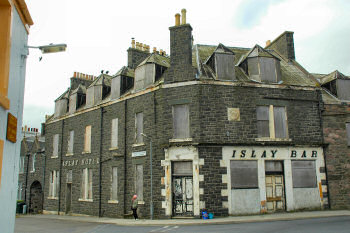 Picture of the front of a dilapidated building, the former Islay Hotel in Port Ellen
