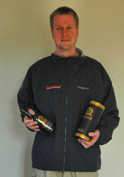Picture of Armin wearing a jacket with a Bunnahabhain logo, holding a Bunnahabhain bottle