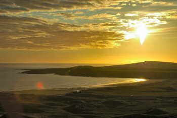 Picture of a sunset over a low hill near a bay on Islay