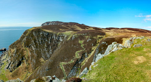Picture of a panoramic view over some steep cliffs with some walkers on the top of the cliffs