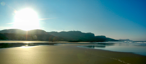 Picture of a beautiful sunrise over a beach flanked by high crags and dunes