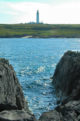 Picture of a lighthouse on the other side of a small sound, a rocky shore in the foreground