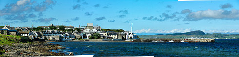 Picture of a panoramic view over a coastal village (Bowmore on the Isle of Islay) with a small pier and harbour