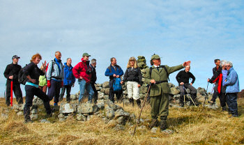 Picture of a gamekeeper with a group of walkers, pointing out a feature