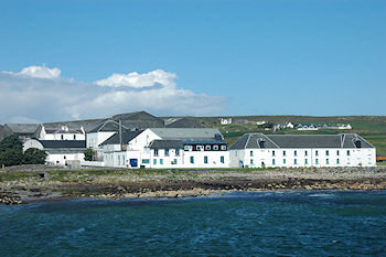 Picture of white washed distillery buildings at a sea shore (Bruichladdich distillery on the Isle of Islay