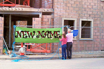 Picture of two people hanging up a sign reading 'new name'