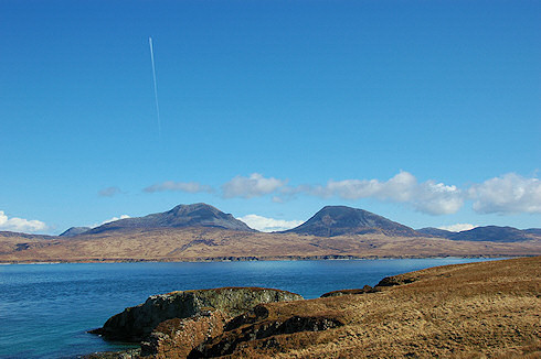 Picture of two round shaped mountains see over a sound, the Paps of Jura seen of the Sound of Islay