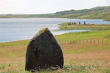 Picture of a standing stone with an island in a loch in the background