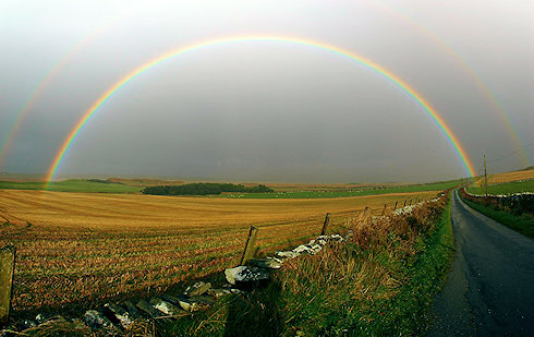 Picture of a full rainbow over an agricultural landscape