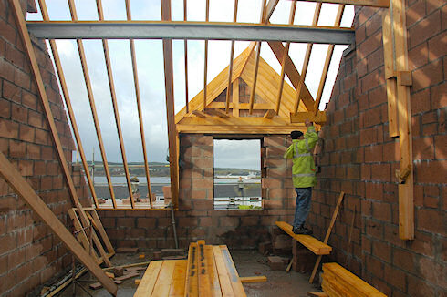 Picture of a carpenter working on a roof, seen from inside of a building