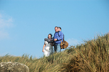 Picture of a photographer with a newly wed couple on the top of a dune