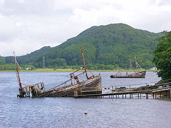 Picture of two fishing boat wrecks at the top of a sea loch