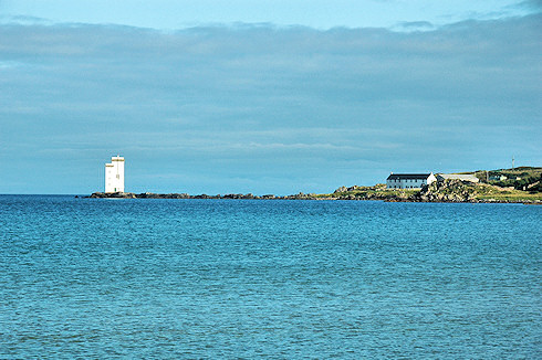 Picture of a calm bay with a lighthouse and house at the end