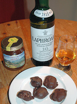 Picture of a plate with chocolate truffles, behind it a bottle of Laphroaig and a glass of honey