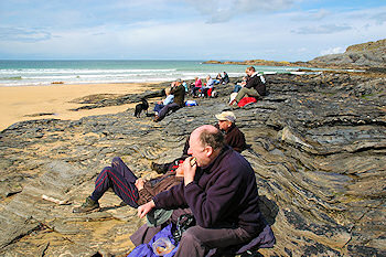Picture of a group of walkers having a picnic on rocks overlooking a sandy beach