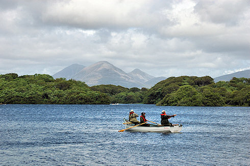 Picture of a boat with anglers on a loch, some distinctive mountains in the background