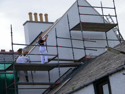 Picture of the gable end of a hotel under construction, workmen just finishing painting it