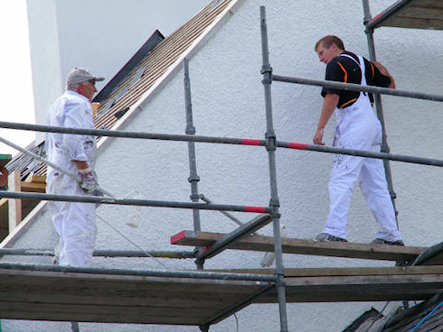 Picture of two men painting a gable end standing on scaffolding
