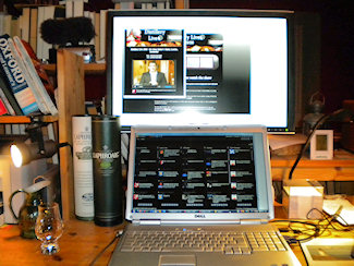Picture of a large monitor and a laptop with the Laphroaig Live event on screen