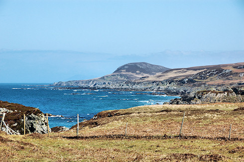 Picture of a view along a wild coastline, various low cliffs and a conical shaped hill at the end