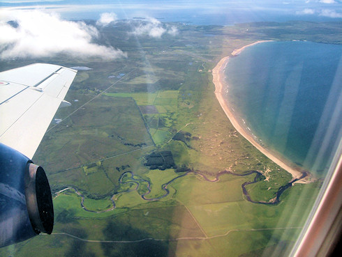 Picture of a wide bay with sandy beach, taken from a plane. A river at the bottom of the picture