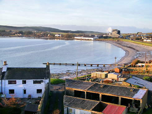 Picture of a view over a bay with distillery warehouses and a maltings at the end