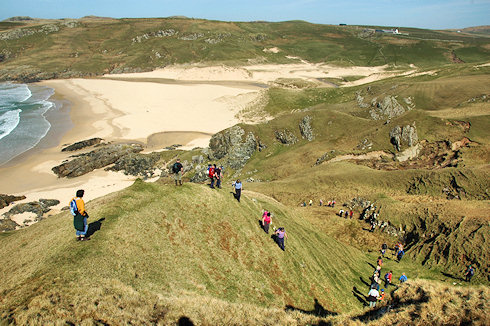 Picture of a long line of walkers descending a hillside towards a sandy beach