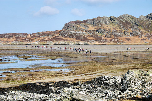 Picture of a large group of walkers crossing a beach between two islands at low tide