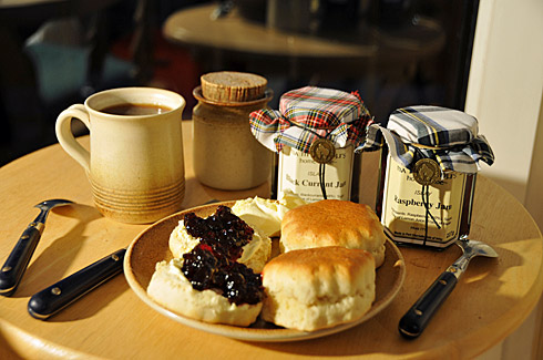 Picture of scones with clotted cream and jam on a plate, glasses of jam behind it