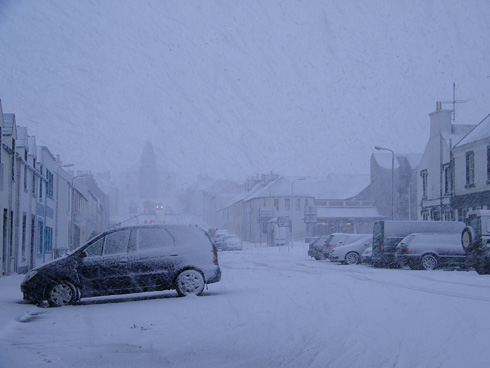 Picture of a heavy snowshower over a village main street (Bowmore, Islay)