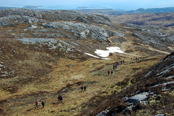 Picture of walkers in a small glen on a hill, some snow on the hillside