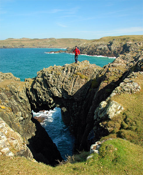 Picture of a walker standing on a natural arch above the sea