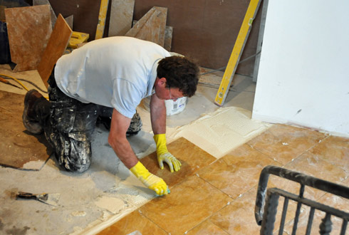 Picture of a man laying floor tiles