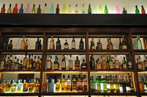 Picture of the shelves behind a bar with lots of whisky bottles