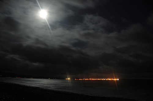 Picture of the Moon breaking through clouds to illumnate a sea loch, a village on the other side
