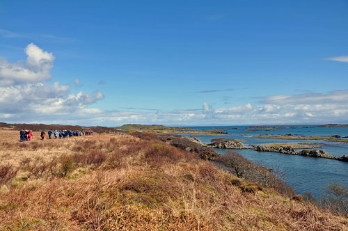 Picture of a group of walkers walking along a shoreline with small islands offshore